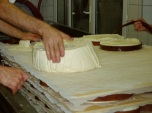 De blok kaas gaat in drieën gesneden worde voor het grote formaat Mont d'Or